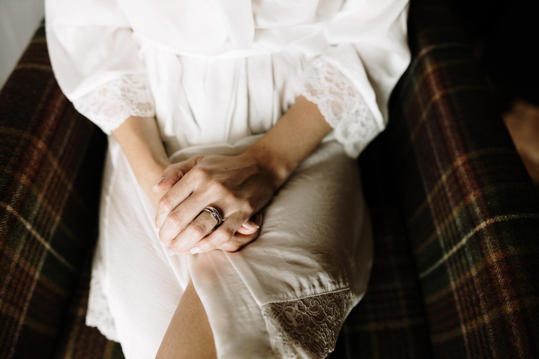 Novia en bata de seda blanca durante su maquillaje
