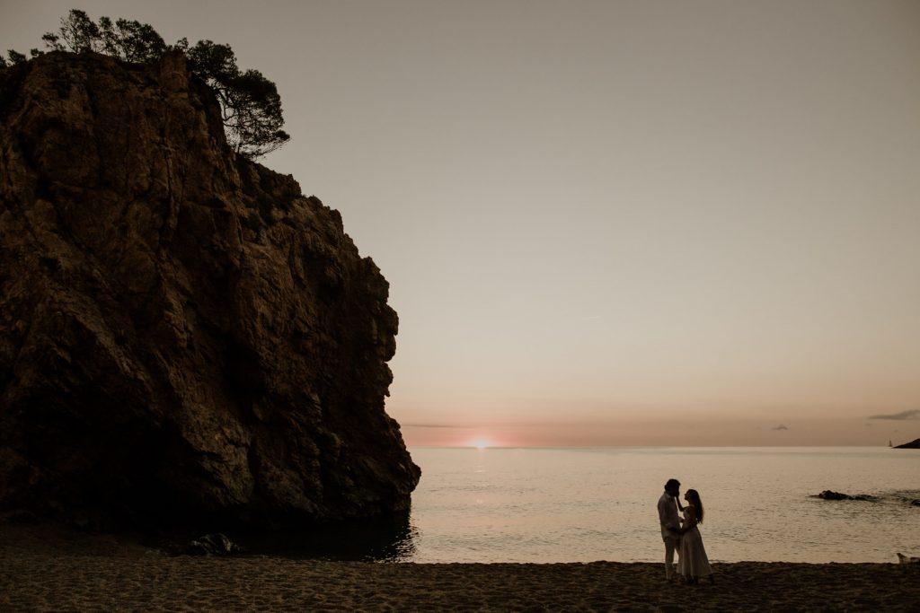 pareja en amanecer en la costa brava en illa roja en su preboda