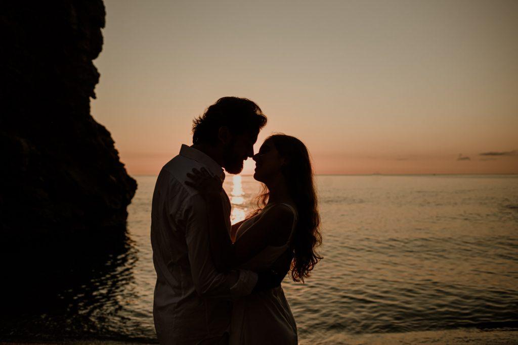 pareja en amanecer en la costa brava en illa roja en su preboda, dos personas abrazadas en una playa de Begur.